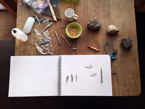 A table covered in drawing materials and a sketch pad